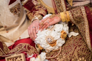 Bride and groom wedding rings placed on a white and gold bouquet at an Asian wedding