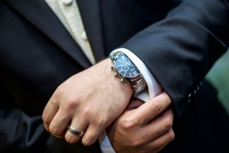 Groom getting ready on his wedding day wearing a black suit, Hugo Boss watch and ring