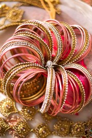 Silver wedding ring in the middle of gold, pink and silver bangles