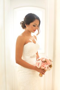 Asian Bride dressed in white wedding dress holding a pink flower bouquet