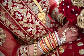 Gold and red embroidered asian wedding dress with gold bangles and jewellery