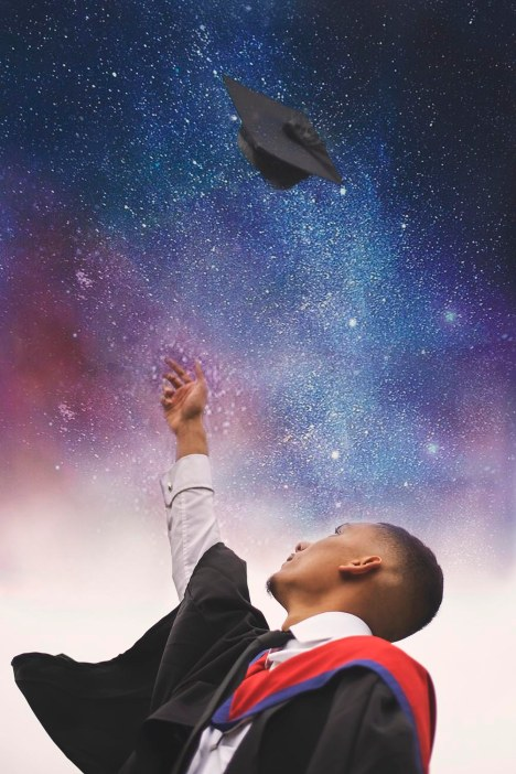 Student throwing hat in the air on his graduation