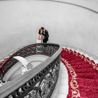 Bride and groom on their wedding day posing on the spiral staircase inside the Luton Hoo Hotel
