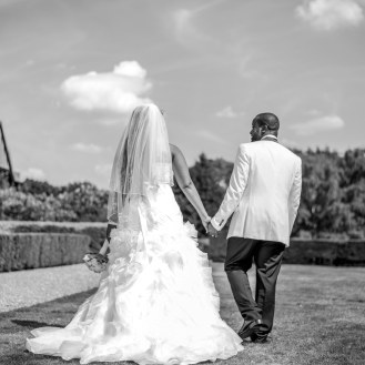 Bride and groom taking a romantic stroll on their wedding day at Putteridge Bury